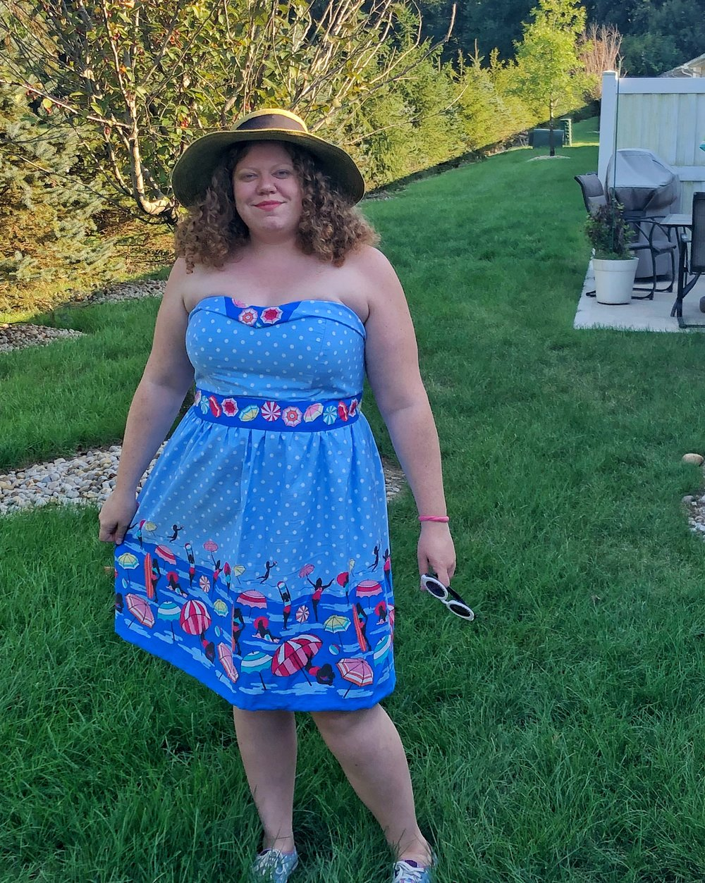 Woman with curly auburn hair standing outside with a sun hat on wearing a blue polka dot dress with pinups in swimsuits printed on it