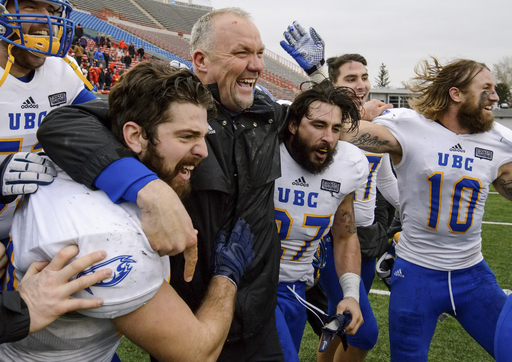 UBC Thunderbirds head coach Blake Nill, centre, celebrates with his team as the 79th Hardy Cup game against the U of C Dinos finishes at McMahon Stadium in Calgary, Alta., on Saturday, Nov. 14, 2015. The UBC Thunderbirds took the  Canada West Universities Athletic Association Football Conference championship game 34-26. Before he coached the UBC Thunderbirds, Nill was the head coach of the U of C Dinos, where he led the Dinos to three Vanier Cup games (2009, 2010 & 2013) and six straight Hardy Cup Championships (2008-13).  (Photo by Maxwell Mawji/ www.CaptureCandy.com)