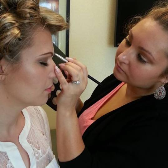 Cristin applying makeup to one of her brides.