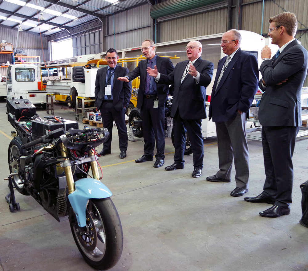 Pictured: Minister Barilaro (left) shares a laugh with Jeff Phillips (second left) whilst inspecting Varley's electric superbike.