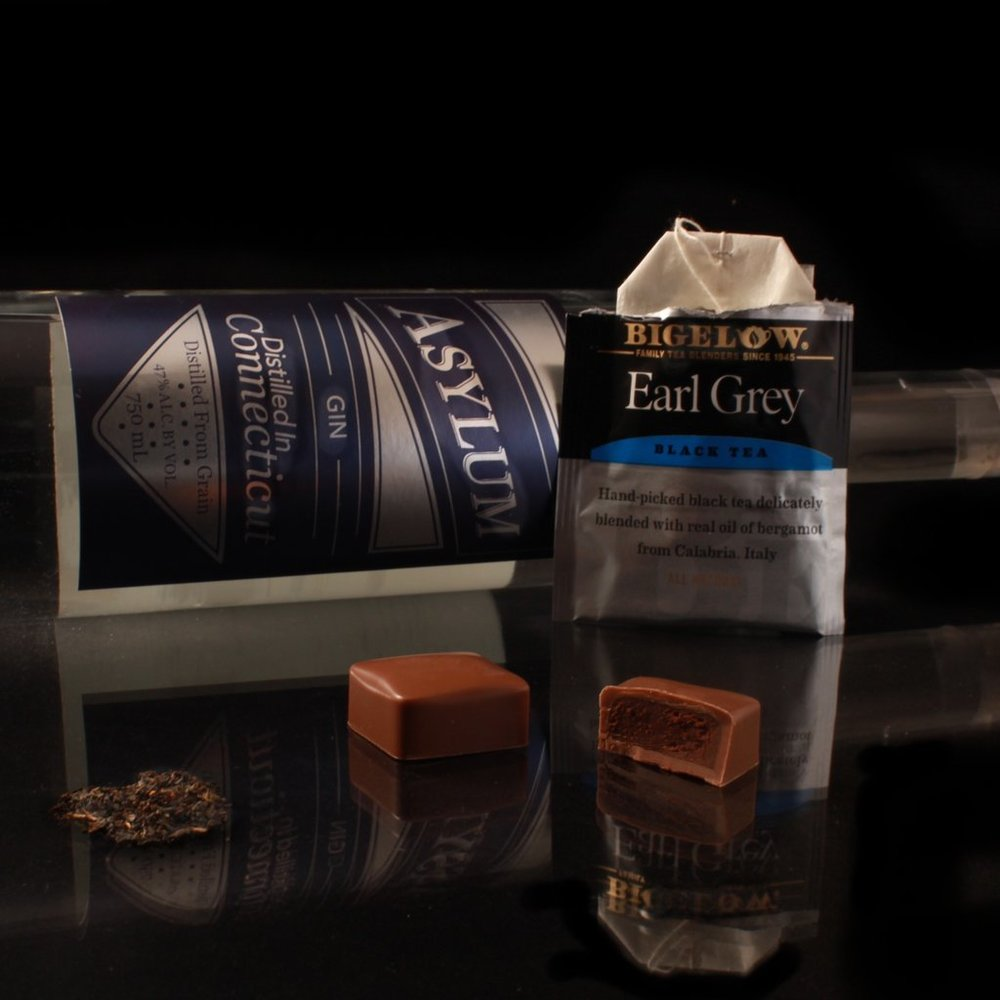 Gin & T    This entertaining ganache pairs two local favorites:  Asylum  Gin with Bigelow Tea. It is a fresh and fun combination of antioxidants, tannins and milk chocolate.  Side note: ¨ T¨ for Tea ! But Also to make you think of a well know cocktail, Gin and Tonic ;-)