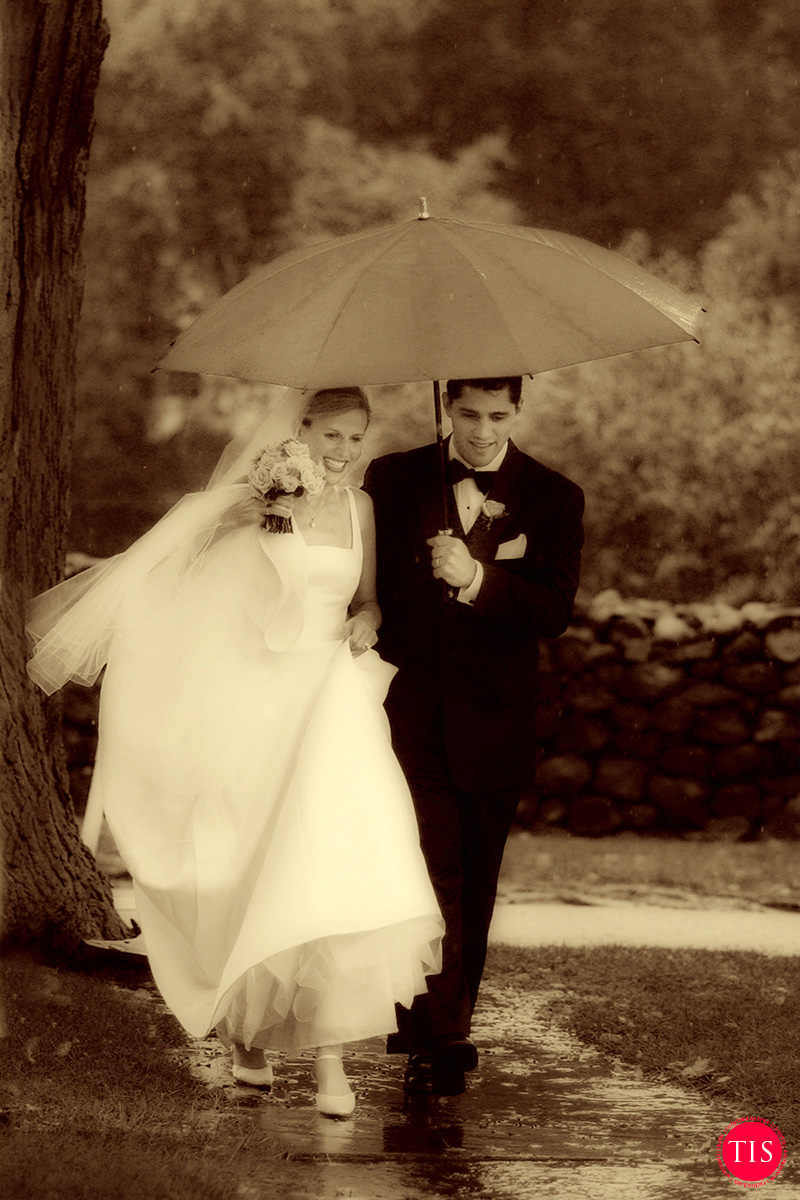 A bride and groom walk in the rain headed towards their tented reception at a private wedding venue in Connecticut. Moment captured by Maring Visuals