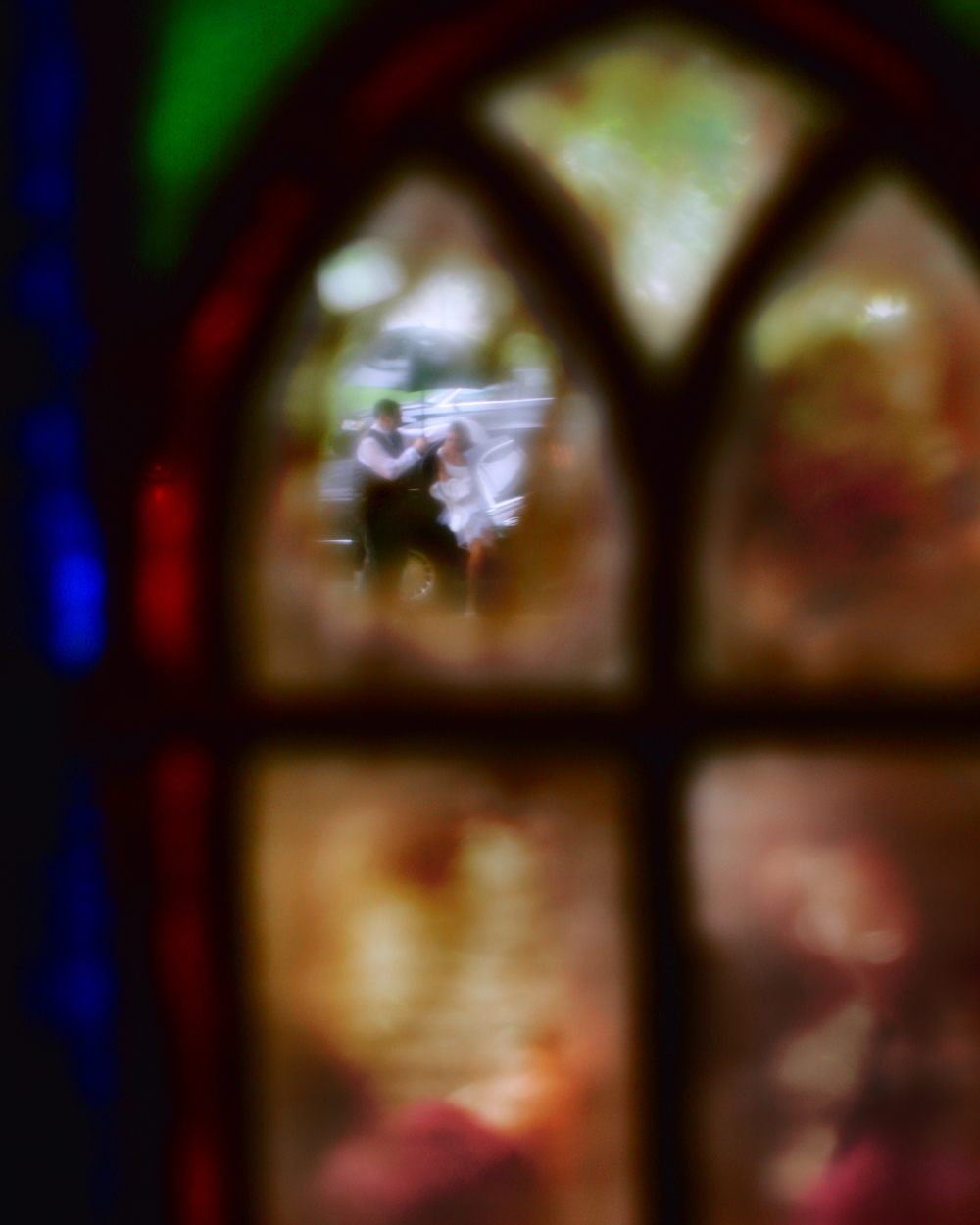 A bride rushes in from the limo to the church captured through a stained glass window in Connecticut. Moment captured by Maring Visuals