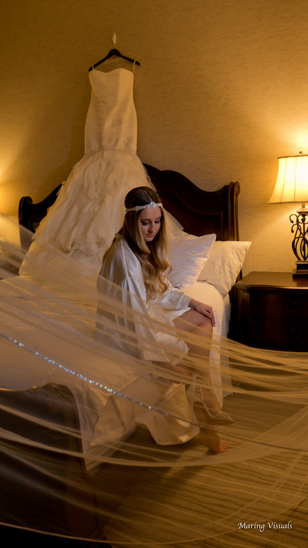 The bride slips on her shoes amidst her dress and veil service as the perfect decor.