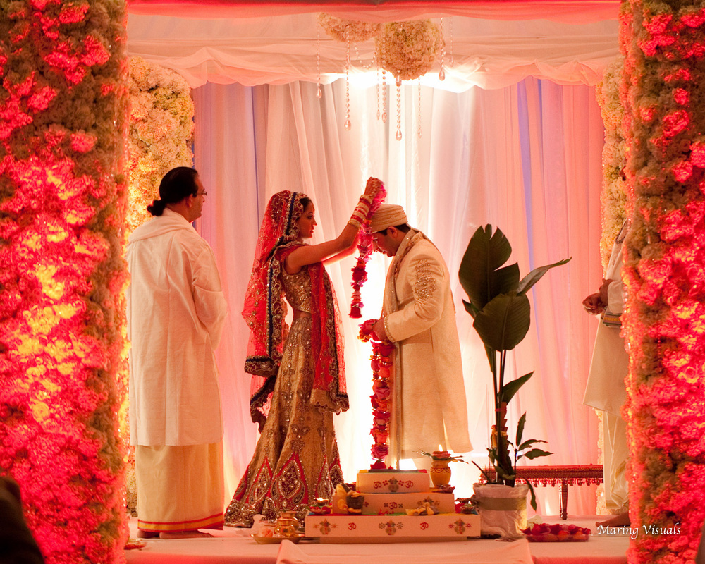 The bride and groom exchanage garlands during their traditional hindu ceremony