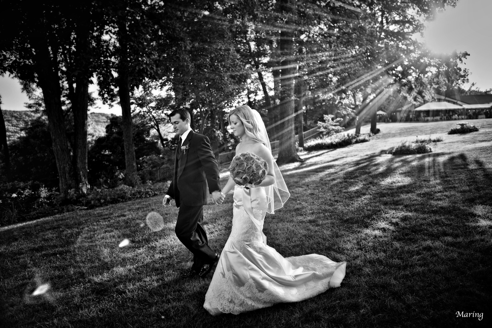 A couple takes a walk down to the river side at their wedding in Connecticut to spend some alone time together before headed to their cocktail hour.