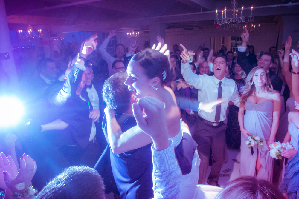 The groom lifts the bride and spins her around as guests cheer them on the dance floor. Make sure to spend time alongside your friends, but with a sense of togetherness as this couple did so well.