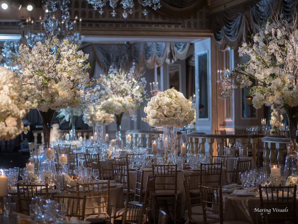 A lavish floral display by Carroll's Florist at The Pierre Hotel with gorgeous room lighting by Maring Visuals