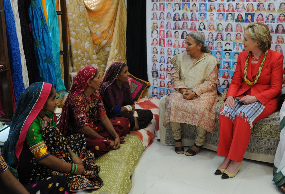 Secretary of State Clinton visiting Mumbai in 2009. Clinton listens to female artisans describe their work with SEWA which enabled them to be economically self-sufficient.