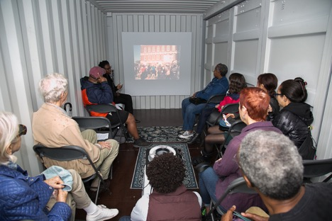 Sabrina Dorsainvil presents a slide talk in the Slideshow shipping container at HUBweek. Photo by Jean Hangarter