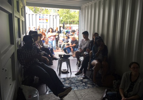 Viewers inside and outside of the  Slideshow  shipping container await a slide talk. Photo courtesy of the artist.