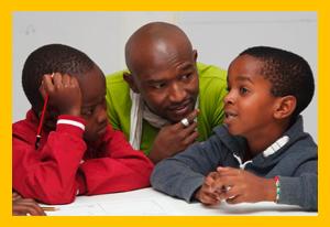 A teacher helps two children thinking through their idea