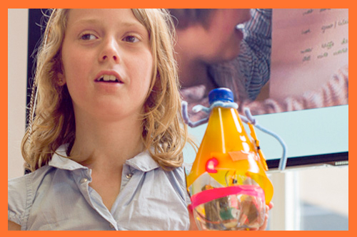 Een meisje presenteert haar zelfgemaakte lamp op zonne-energie