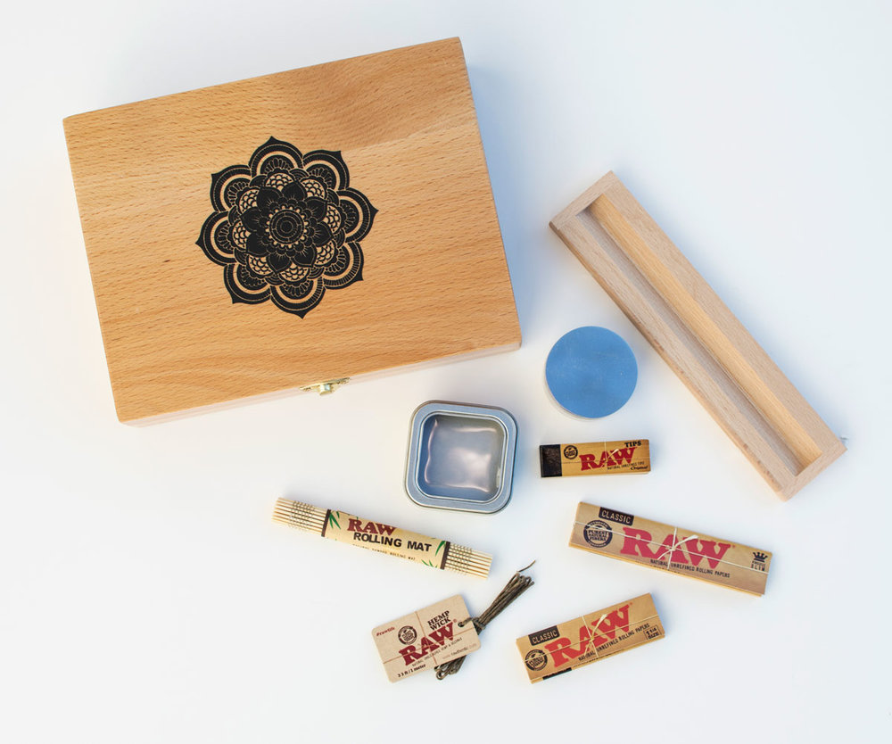 "Outside of the box and its contents: RAW rolling mat, hemp wick, regular and large rolling papers, filter tips and a grinder, small container, and removable magnetic ""rolling sleeve"""