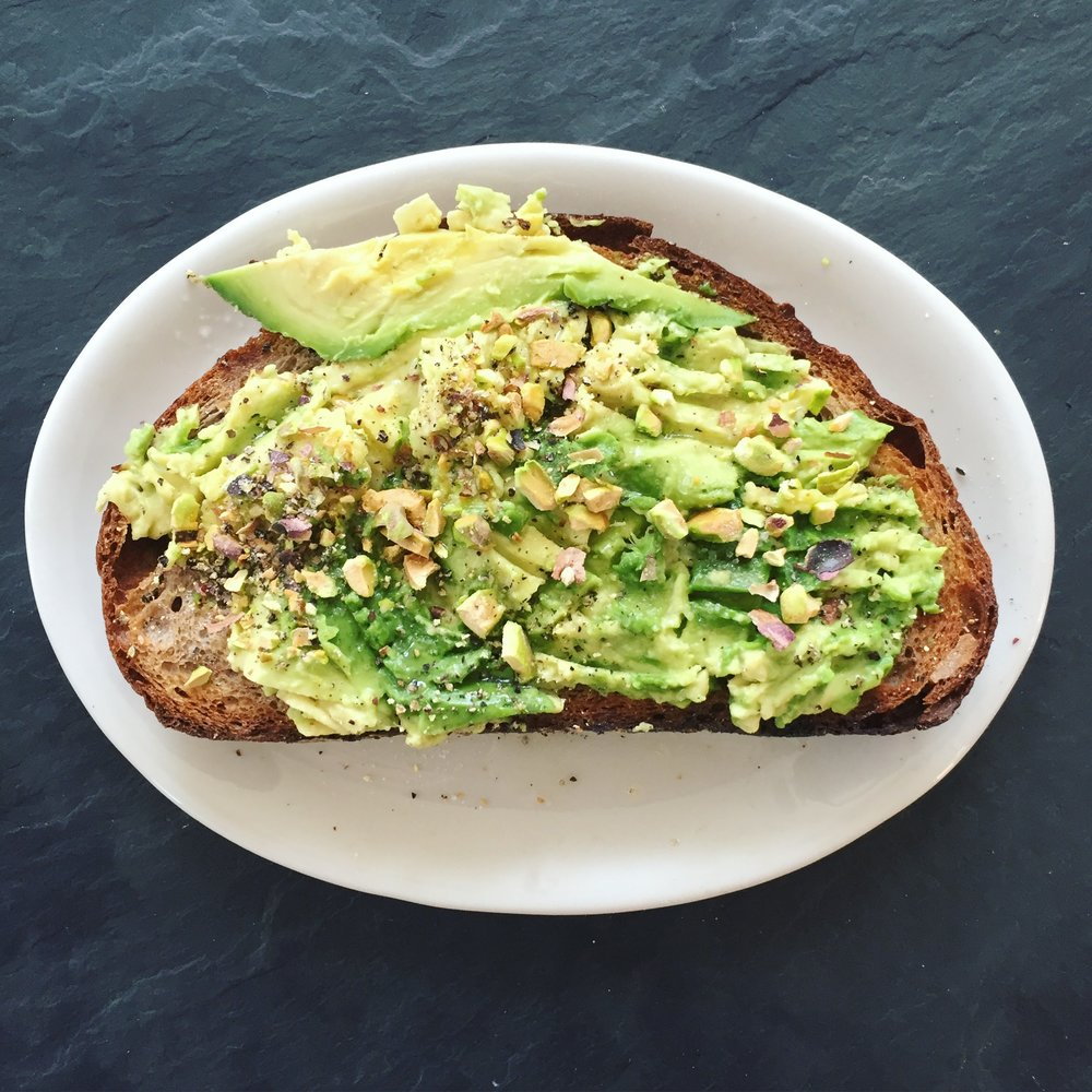 Avocado on walnut bread with olive oil and crushed pistachio.