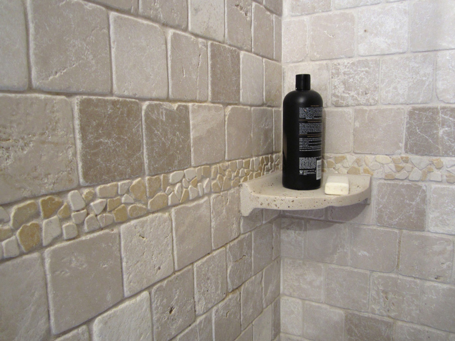 Tumbled marble shower walls, stone mosaic chair rail