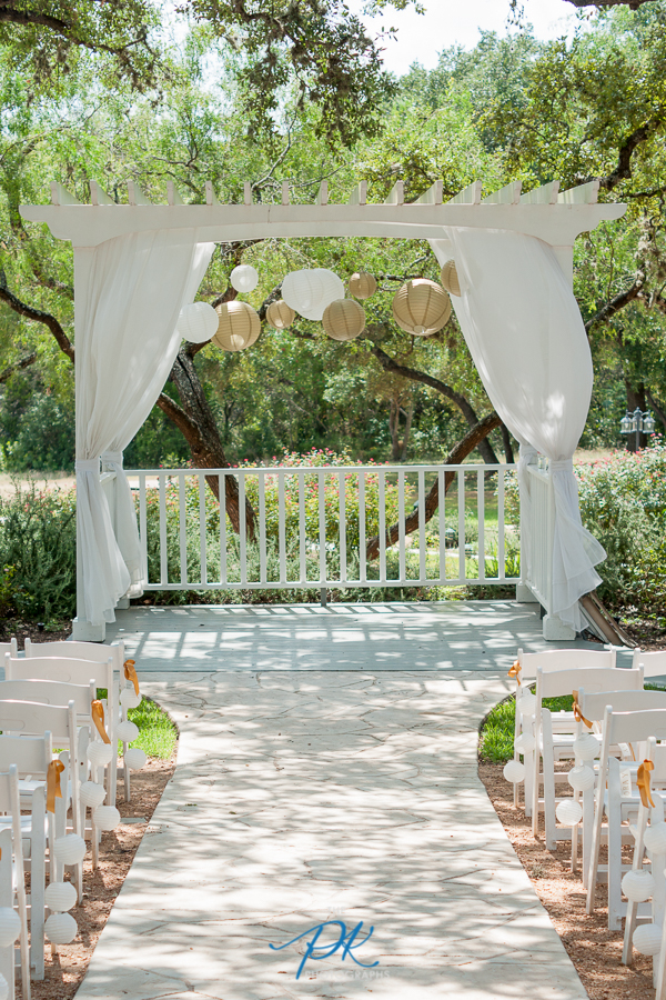 The ceremony area at Gardens at Old Town Helotes was perfectly decorated in all gold and white.