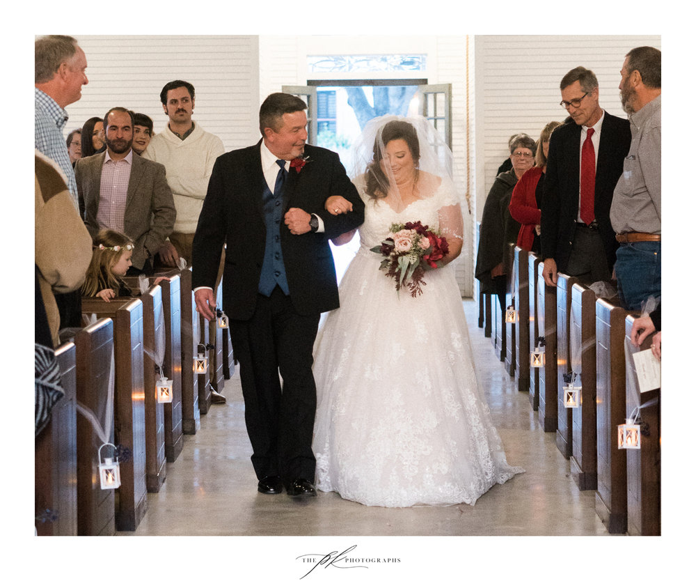 Emily and her father walking up the aisle at the Chandelier of Gruene.