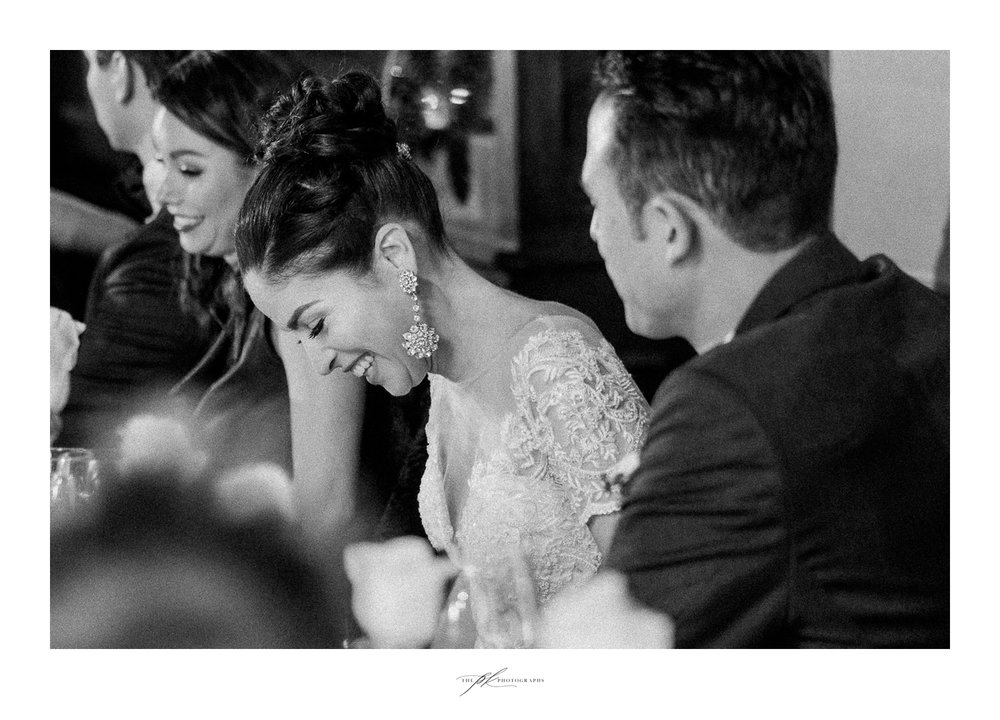 The bride laughing during toasts at her wedding reception.