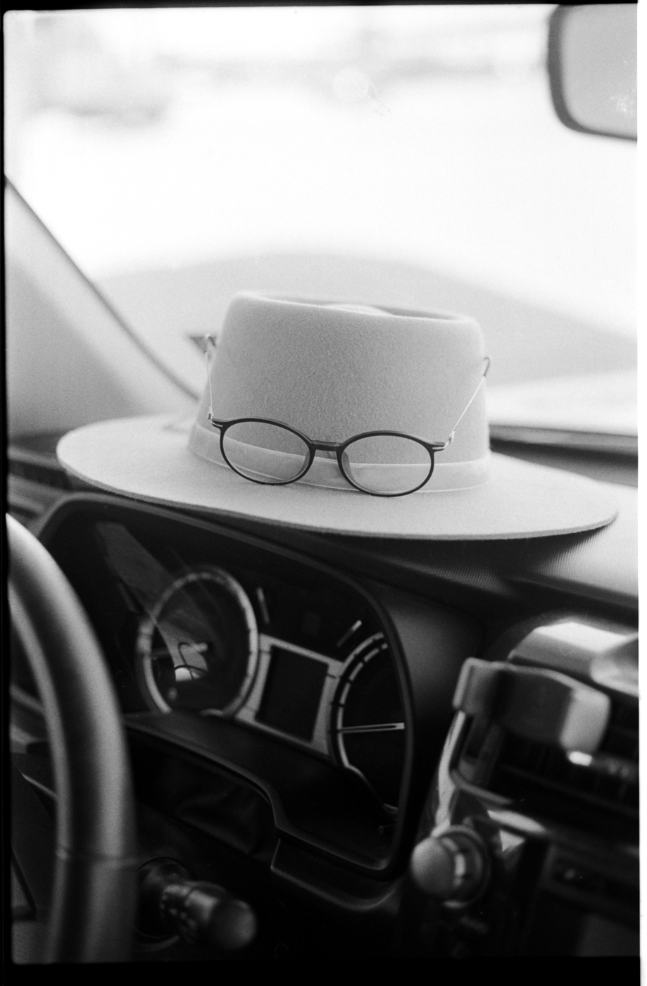 May's glasses and hat sitting on her dashboard while we waited for her battery to be changed. #spoileralert  Captured, developed and scanned by Parker on  Ilford HP5+  | 35mm
