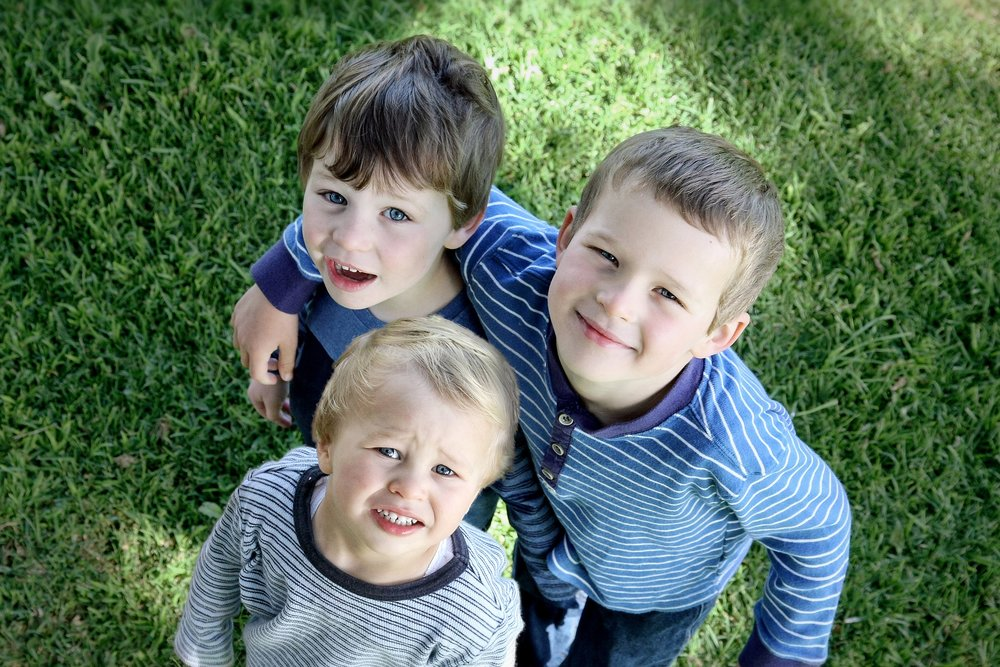 Stock photo of three brothers looking up at camera