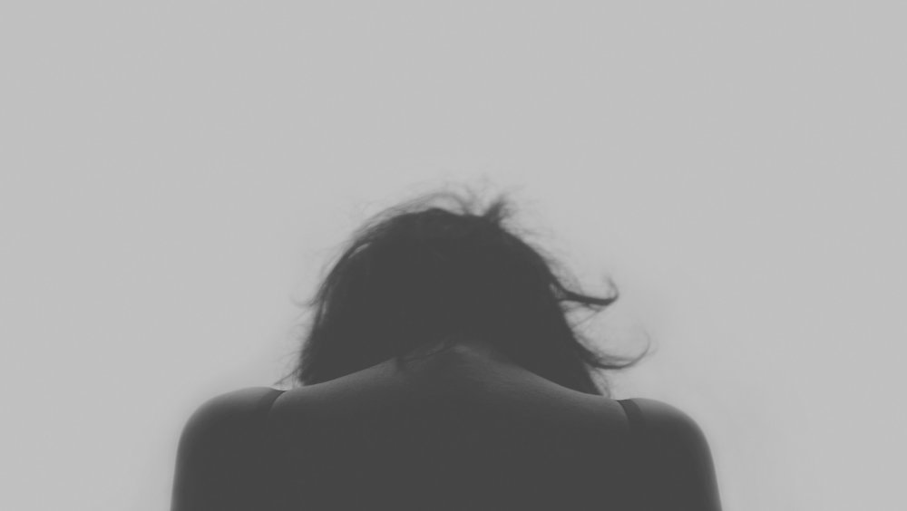 IMG: Black-and-white photo of a woman's head and shoulders from the back, hunched over