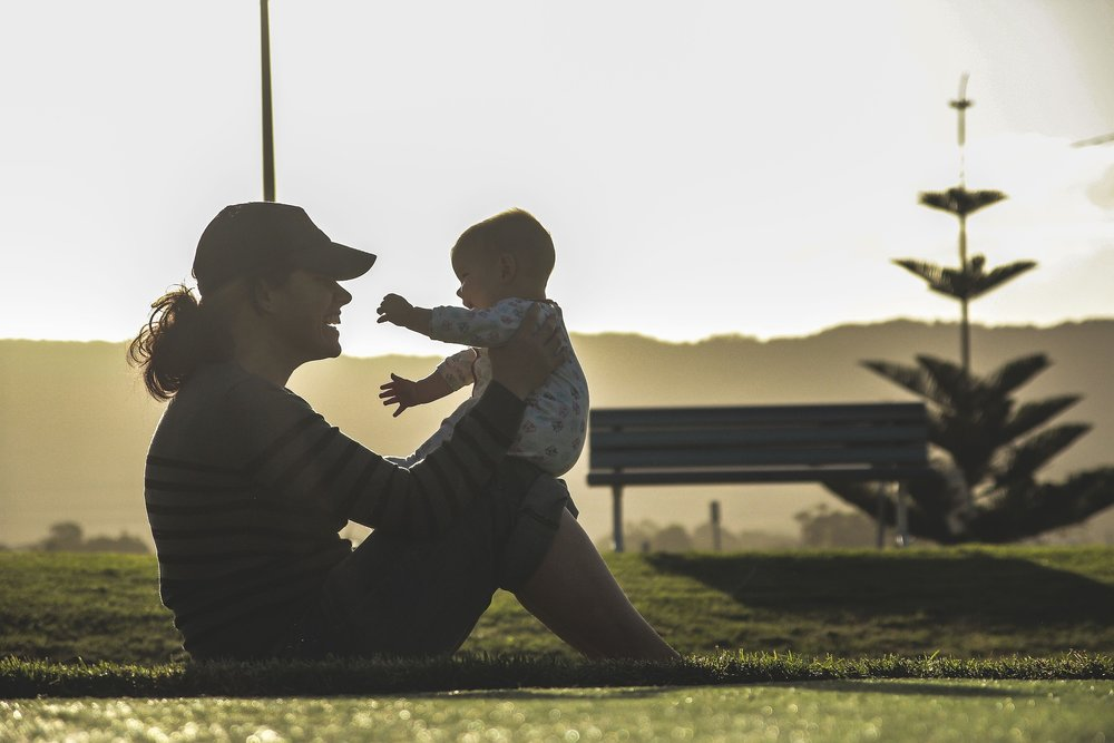 Stock photo of mom sitting in field playing with baby