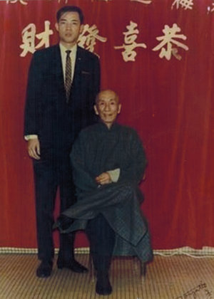 Grandmaster Moy Yat (left) with his Sifu, Grandmaster Yip Man (seated).
