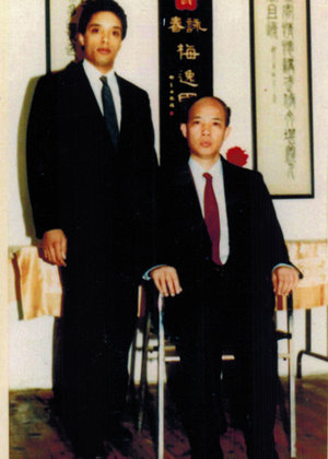 Grandmaster Moy Tung (left) with his Sifu, Grandmaster Moy Yat (seated).