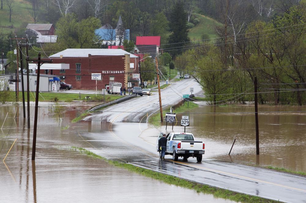 Motorists travel over a flooded State Route 550 in Amesville Wednesday, April 20, 2014. The Federal Creek runs through Amesville, which has a history of large floods. In 1998, floodwater in Amesville ruined houses in what if now Gifford Park.