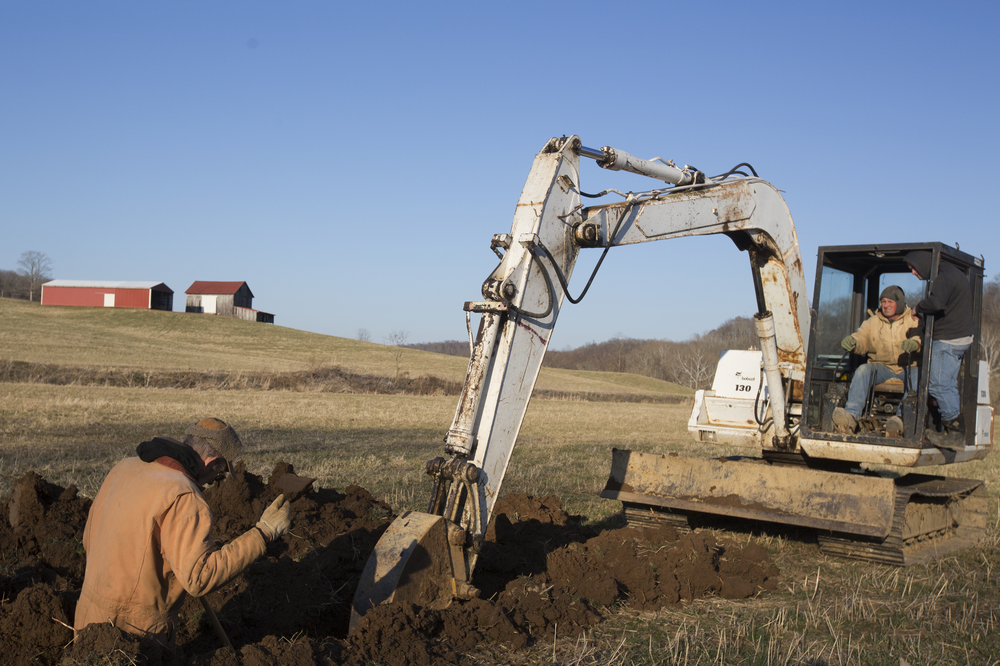 From left, Richard Brown signals to Jeff McKibben and his son Jerry McKibben while digging a ditch. They were digging to put in a gas line for McKibben's neighbor Ben Kasler.