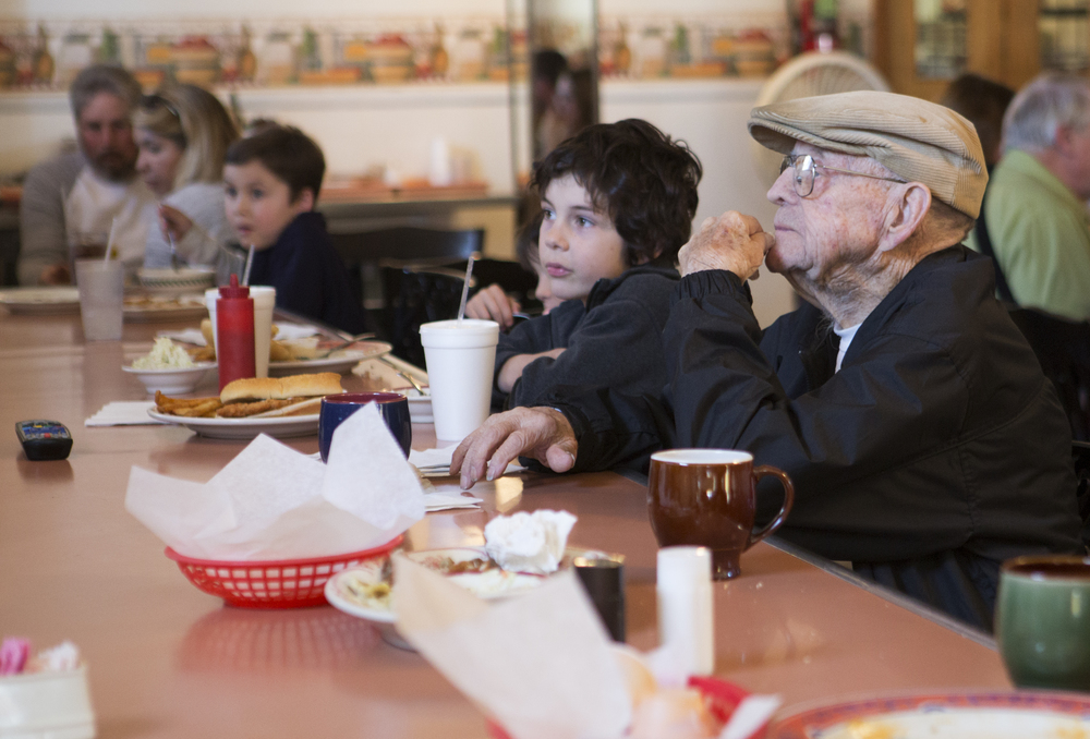 From right, Dwight Groce from The Plains, sits at the counter at Kasler's Country Kitchen in Amesville while Riley Russell, 8, and Cort Russell, 5, from Sharpsburg, watch the television in the restaurant on a crowded Sunday afternoon.