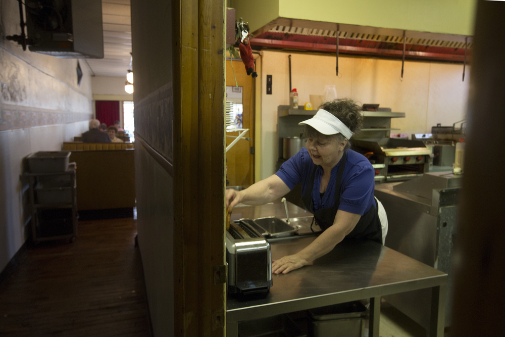 Janis Hill leans forward to grab a piece of toast while working in the kitchen at Kasler's Country Kitchen.  Hill works in the restaurant six days a week.