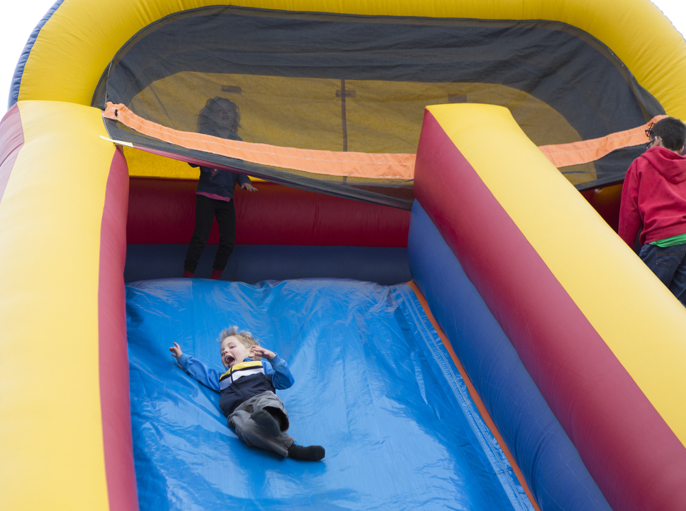 Hudson Young, 4, rides down an inflatable slide behind Amesville Elementary School during a school carnival.