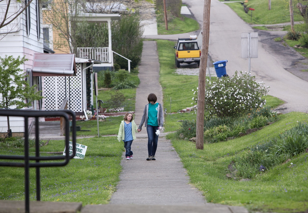 Kaylee Ford, 5, walks with her neighbor, Sonya Ferrier, 16, along North Franklin after picking up trash in Amesville during the Amesville Presbyterian Church parish lock-in.