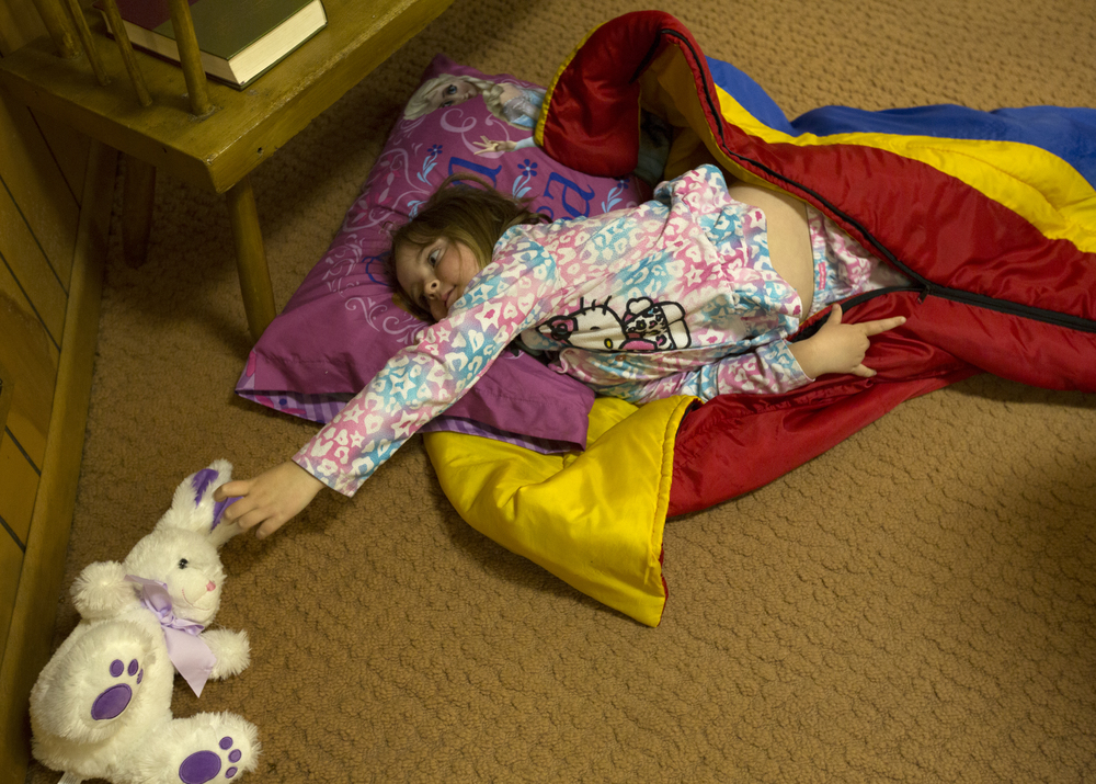 Kaylee Ford, 5, reaches for her stuffed bunny rabbit while settleing in for the night in the Amesville Presbyterian Church during the parish lock-in. Ford was given the bunny for Easter.