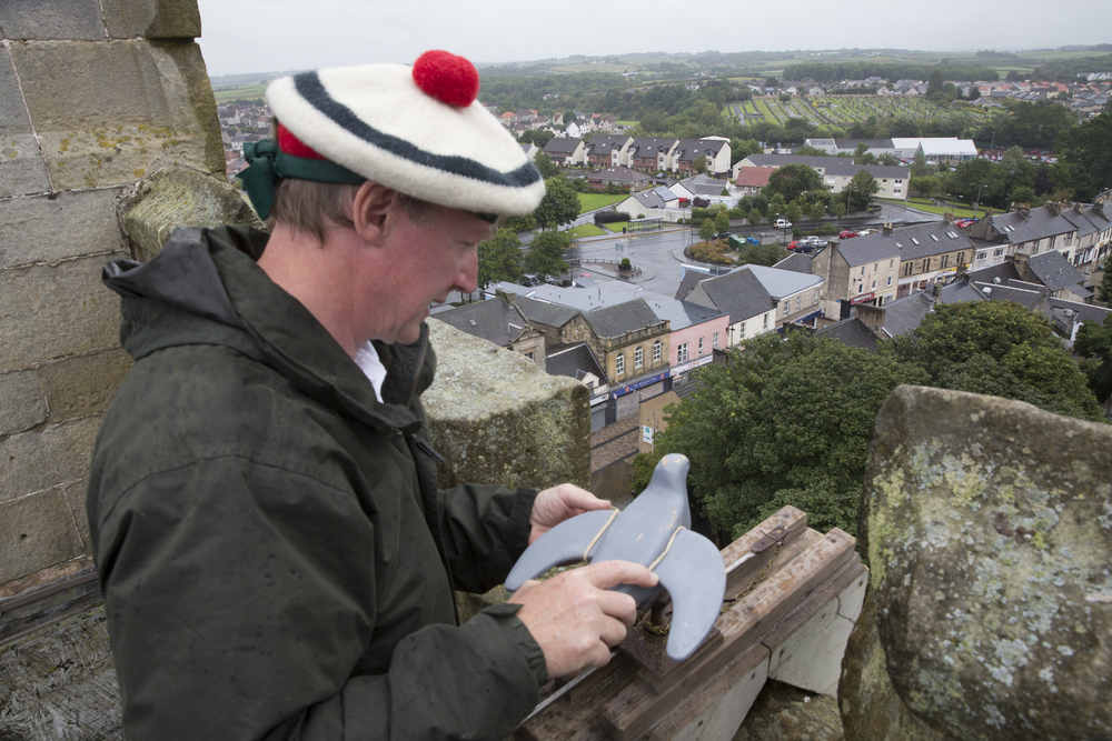 Jim Bilby, of the Ancient Society of Kilwinning Archers, sets the wooden pigeon at the top of the Kilwinning Abbey Tower for the open Papingo in Kilwinning, Scotland.