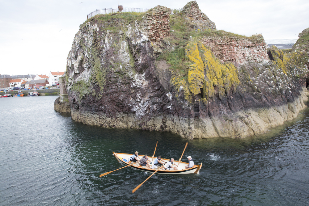 "From right; Kenny Maule coxes ""Black Agnes"", rowed by Alistair Mackie, Diana Mackie, David Northcott, and Pamela Maule into Victoria Harbour in Dunbar, Scotland."
