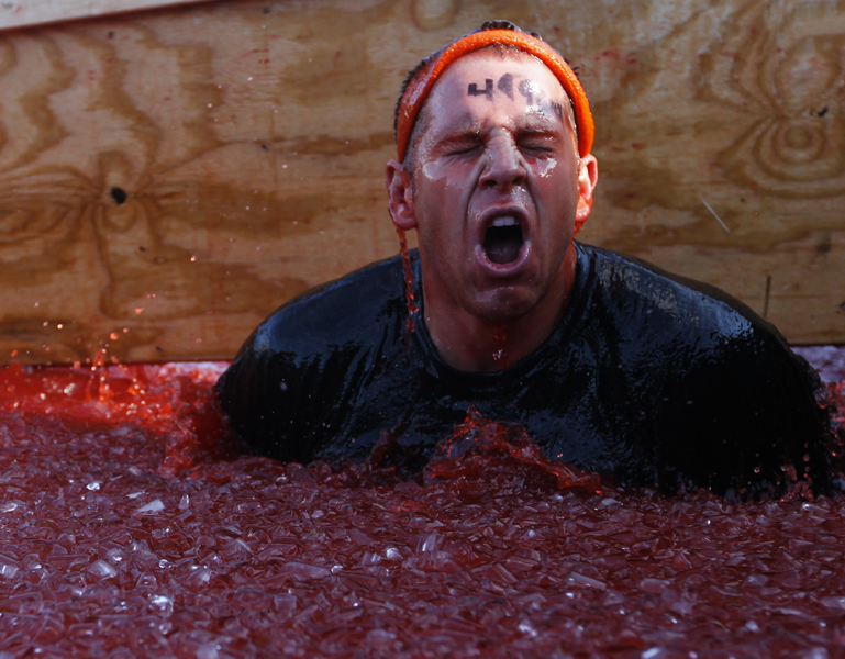 "A Tough Mudder emerges from a dumpster filled with ice and water during the obstacle ""Chernobyl Jacuzzo"" in the Tough Mudder event at Wintergreen Saturday, Oct. 22, 2011.  Copyright: The Daily Progress"