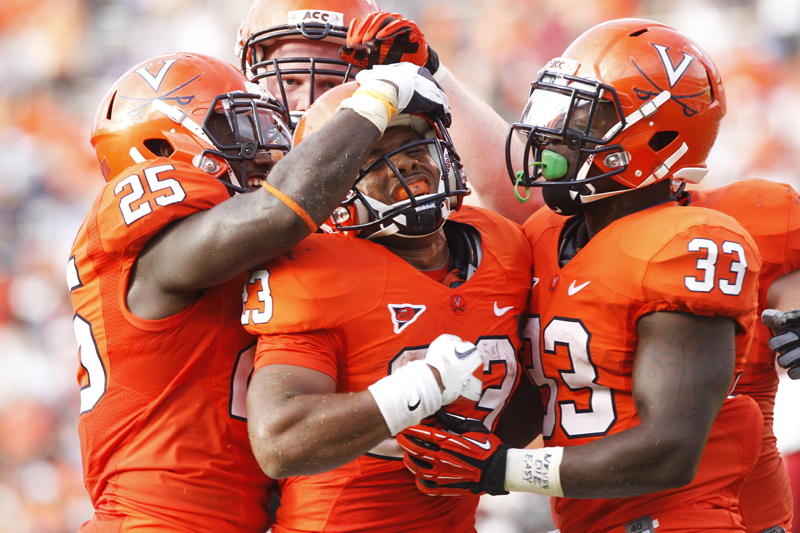 Virginia Cavaliers' Kevin Parks (25) (left) and Perry Jones (33) (right) surround Khalek Shepherd (23) (center) after Shepherd scored a touchdown against the Richmond Spiders at Scott Stadium Saturday, Sept. 1, 2012.  Copyright: The Daily Progress