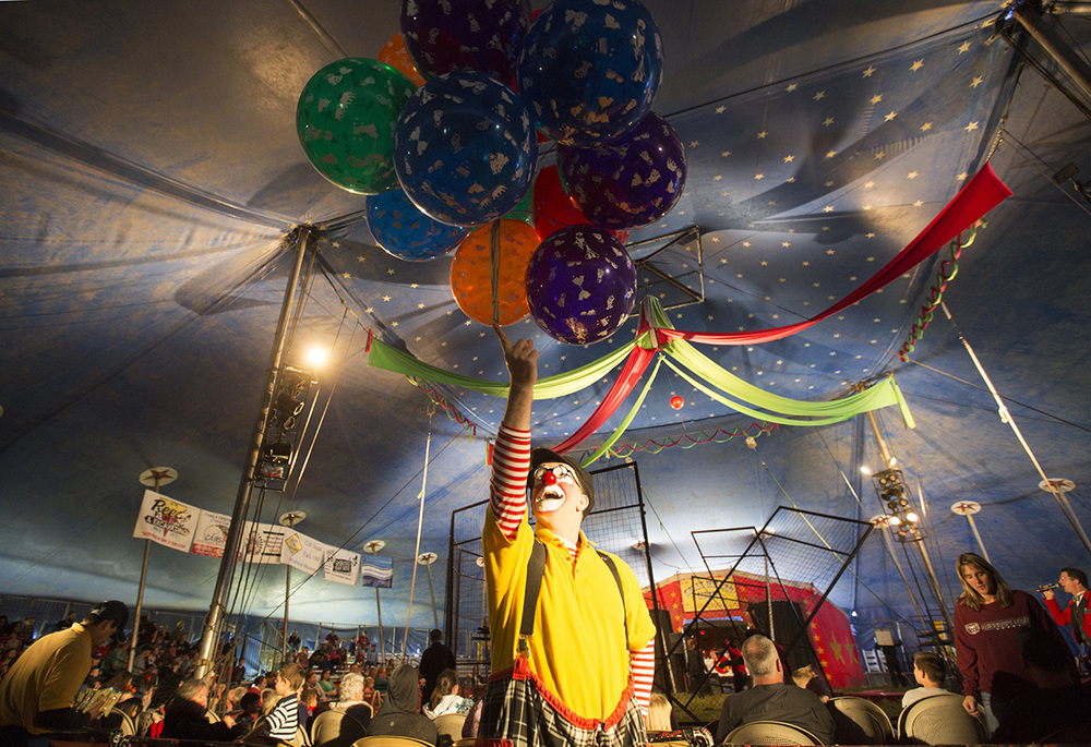 John Sayre, aka J.P. Ballyhoo, balances balloons on his finger while vendors sell peanuts to the crowd and the crew prepares the arena for the next act.
