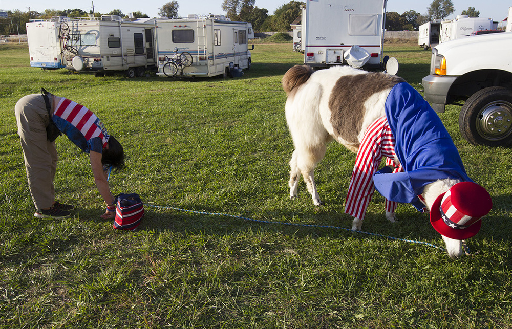 Carolyn Rice stretches while Uncle Sam, the llama, snacks behind the tent just before the intermission of the show.