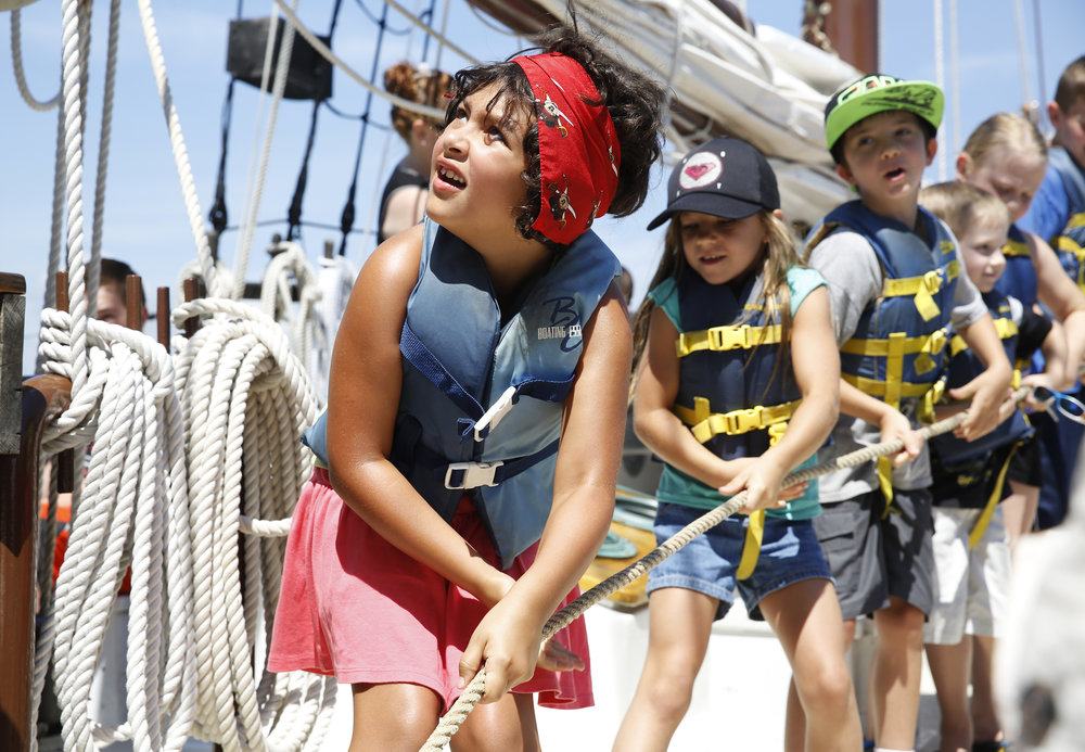 Kara Flexer (from left), 7, from Delaware, looks up at the mast as she works to raise it on the Alliance alongside Rowan Reed, 7, and Jake Reed, 8, from California, Wednesday, June 29, 2016. They were sailing with the Yorktown Sailing Charters' pirate cruise. Copyright: The Daily Press