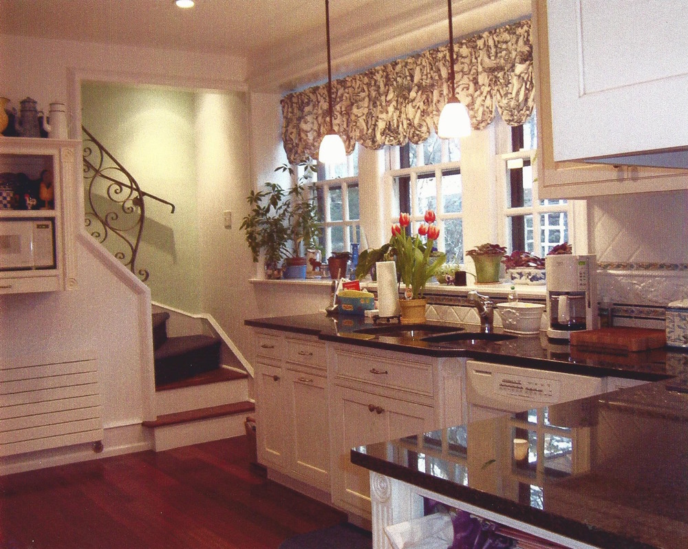 Renovated 1920's tudor house: KItchen with back stairwell opening and custom designed railing