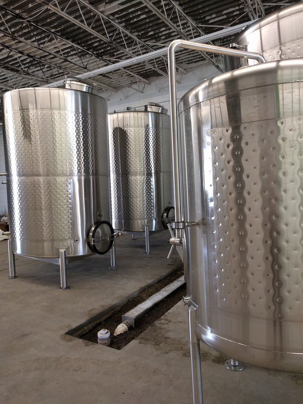 Look at those pretty fermentation tanks and unfinished floor drain!