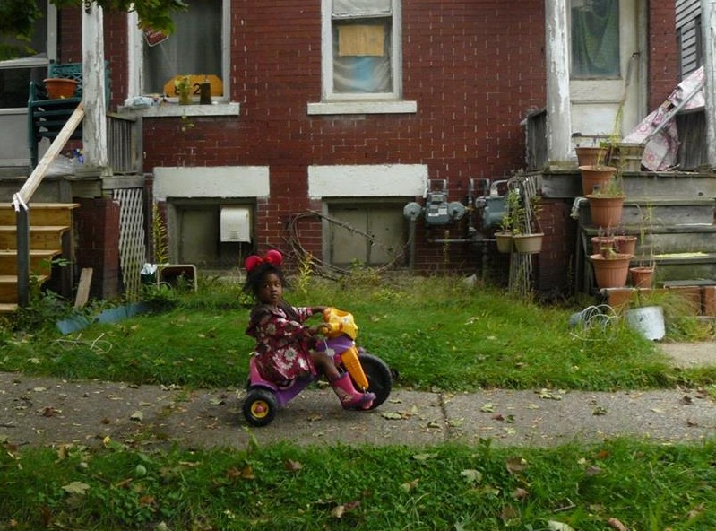 A young girl sits on a Tricycle in Detroit. Photo: Michele Oberholtzer