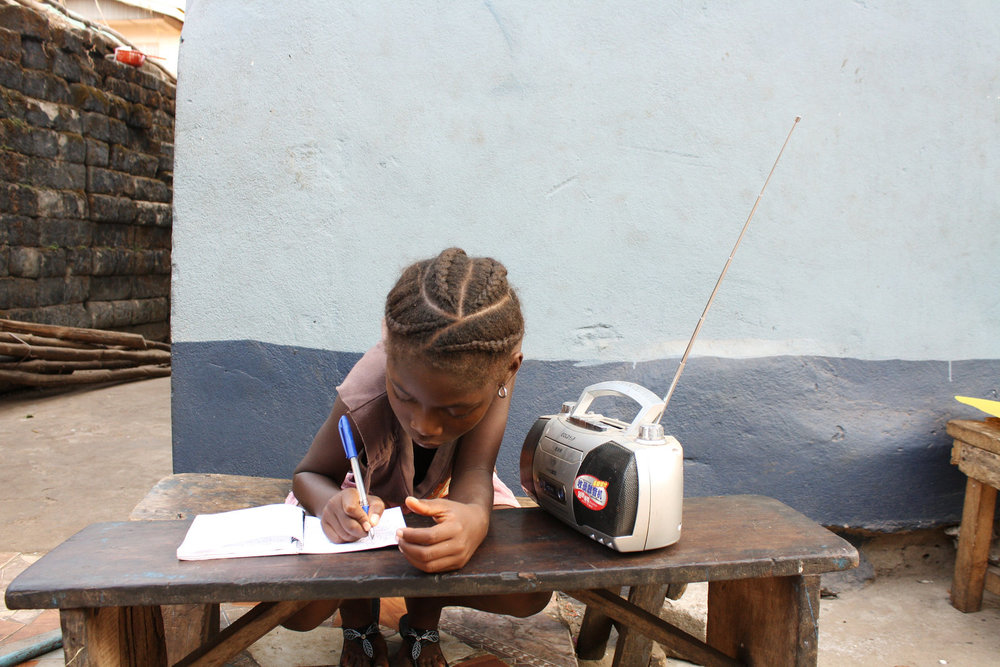 Angela Kamara, 6 years old, takes a lesson from the radio. Tolu Bade/Courtesy of UNICEF