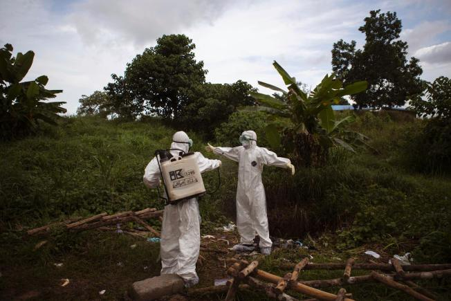 FILE - In this Wednesday, Sept. 24, 2014, file photo, a health worker sprays a colleague with disinfectant after working inside a morgue with people suspected of dying from the Ebola virus, in Kenema, eastern Sierra Leone. An Associated Press investigation has found that the World Health Organization and other responders faced key obstacles in their efforts to stop the spiraling Ebola outbreak in the summer of 2014 in Kenema, a pivotal seeding point for the virus and a microcosm of the messy response across West Africa. (AP Photo/Tanya Bindra, File)