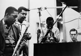 John Coltrane, Cannonball Adderly, Miles Davis and Bill Evans during the recording of  Kind of Blue.   Image via   improvjazz.wordpress.com .