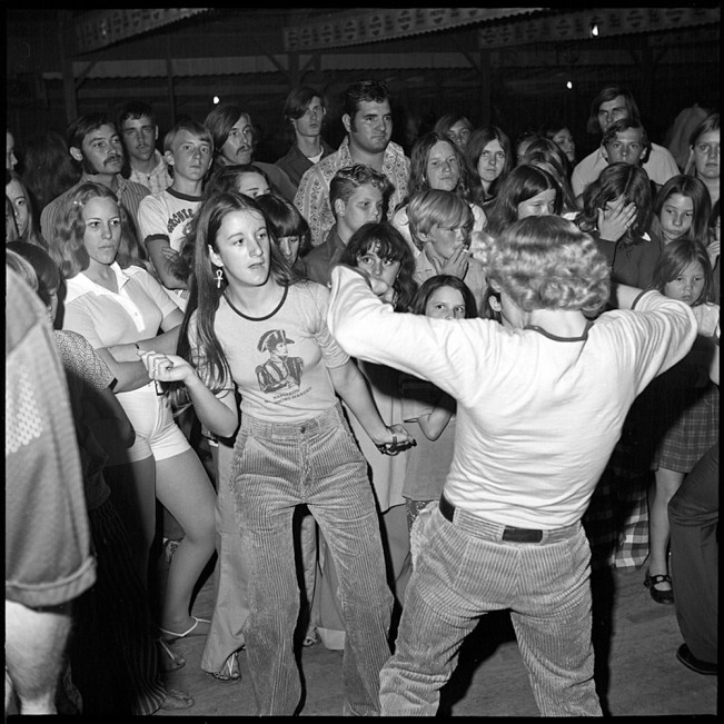 Note the expressions on the faces of the onlookers, who feel something other than swept up by the moves of the dancers in front of them.  Their detachment and, in some cases, defiance opens up and deepens our sense of what is happening in the room.  Photo by Bill Yates.  Image via lenscratch.com.